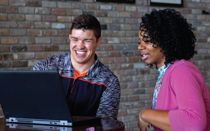Man and woman smiling in front of computer screen
