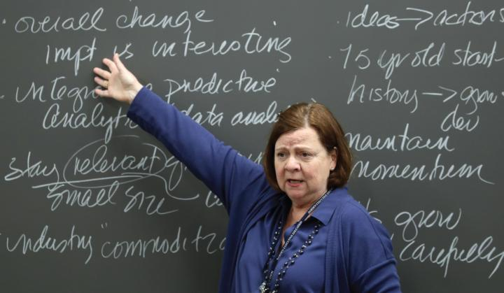 instructor pointing at a chalkboard covered in cursive writing