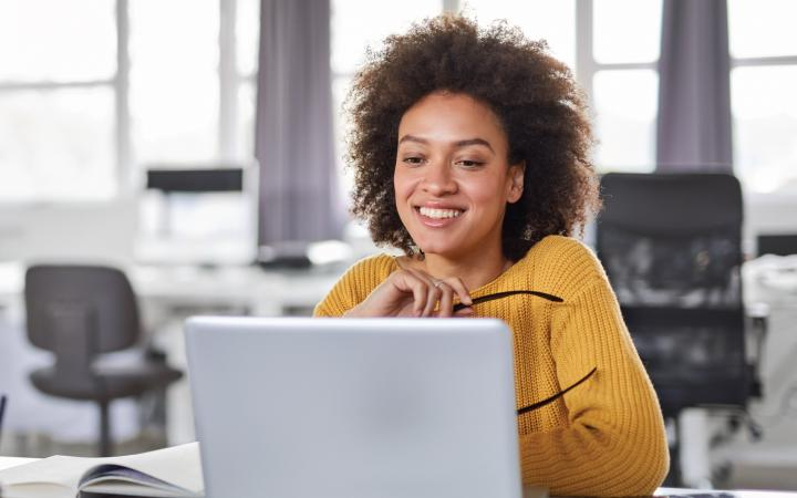 Woman in yellow sweater sitting in front of computer
