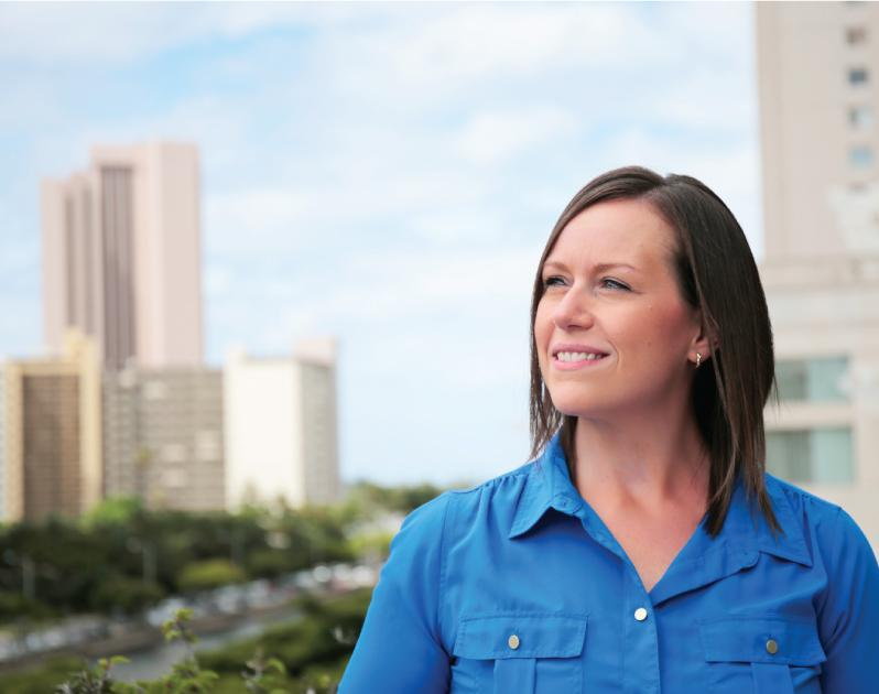 woman smiling and looking left in front of daytime skyline