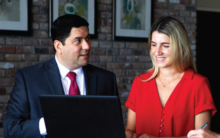 Man and woman talking in front of laptop